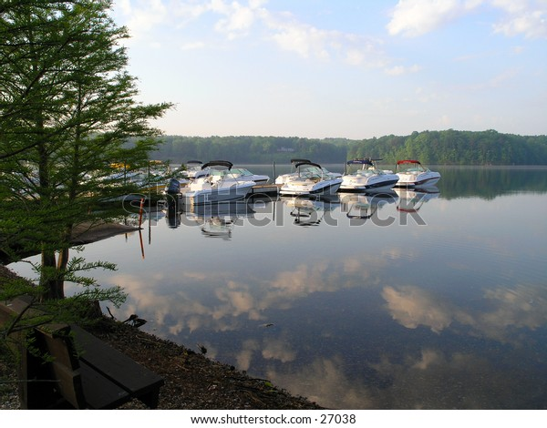 Boats lined up by a dock at the stroke of dawn at a local in-water boat show at Lake Wheeler, Raleigh, NC