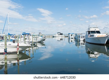 Boats and luxury yachts parked at docks and on hoists in a private yachting club. Long Beach Island, New Jersey ocean boating background