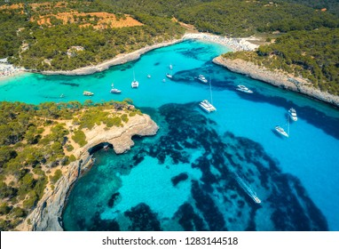 Boats and luxury yachts in transparent sea at sunny day in Mallorca, Spain in summer. Aerial view of sea coast. Colorful landscape with marina bay, azure water, green trees. Top view of shore. Travel