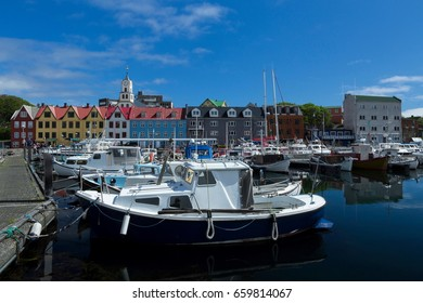 Boats in marina, Torshavn, Streymoy Island, Faroe Islands, with colourful buildings and church in the background