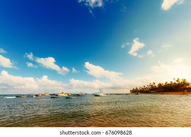 Boats moored during the sunset at the sea in Praia do Forte, Brazil