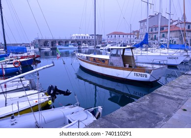boats moored in the harbor of Muggia in a foggy day
