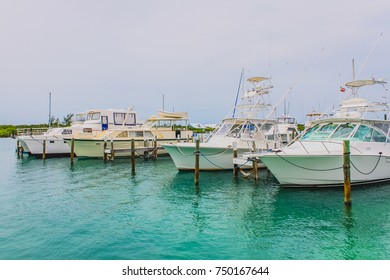 Boats moored inside a marina bay with small wooden pier at Man O War cay, Abaco, The Bahamas.
