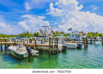 Boats moored inside a marina with small wooden pier at Hope Town Harbour, Abaco, The Bahamas.