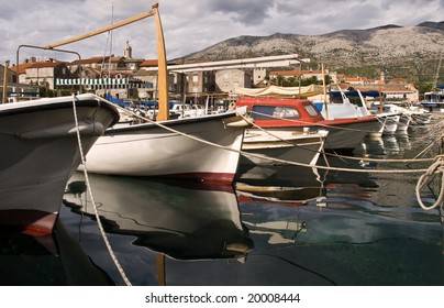 Boats moored in Korcula, Croatia with calm reflections in the sea and mountains in the background.