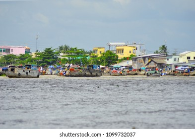 Boats are moored near a village on the Mekong River, Vietnam. Many of the boats have eyes painted on them. The photograph is taken from water level. Yellow and pink buildings are in background.