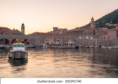 Boats moored in old town pier of Dubrovnik at sunset