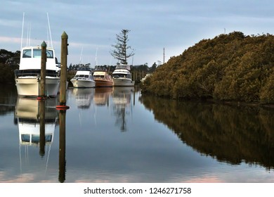 boats moored on a calm river with pole moorings and mangroves along the rivers edge under a cloudy sky and reflections in the water