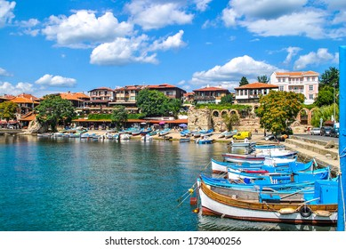 Boats mooring on sea in Nessebar, Bulgaria. Summer sunny landscape with moored woods boat at quay by blue sky