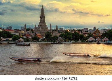 Boats on Chao Phraya River and Wat Arun Temple background before Sunset in Bangkok,Thailand