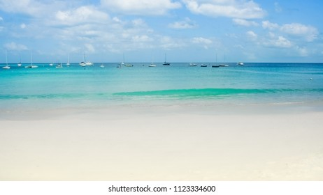 Boats on clear sea and white sand in the caribbean - Shutterstock ID 1123334600