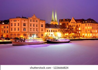 Boats on Frozen Trave river at nights. Lights on Lubeck city embankment. Germany