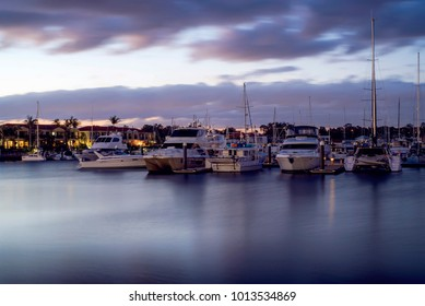Boats on harbour at sunset in Summer. Raby Bay Harbourside, Cleveland, Queensland, Australia