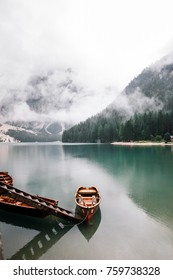 Boats on Lago di Braies mountain lake during rainy day