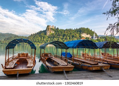 Boats on Lake Bled with Bled Castle high up on a cliff in the background