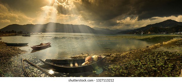 boats on lake in pokhara at sunset