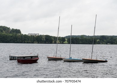 Boats on the lake view on a cloudy day with a cloudy sky and trees in the background
