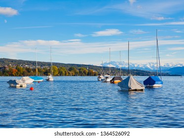 Boats on Lake Zurich in Switzerland in the evening at the middle of autumn, summits of the Alps in the background - view from the city of Zurich.