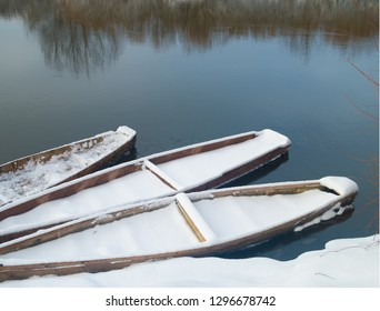 boats on the shore of the river winter