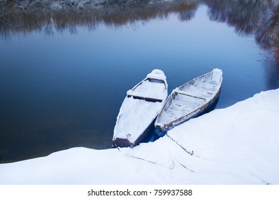 boats on the shore of the snowy river