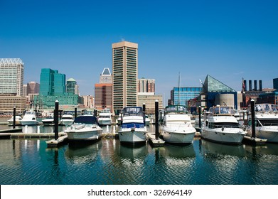 Boats on the water of Baltimore, Maryland's Inner Harbor with city buildings in the background against a clear blue sky