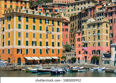 Boats on the water in a small bay and colorful houses on background in small town of Camogli, Italy.