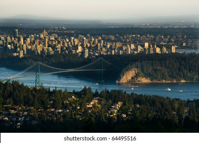 Boats pass underneath Lions Gate Bridge in Vancouver with Downtown skyline behind.
