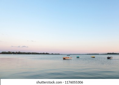 Boats and pedalos resting on the blue waters of Palic Lake, in Subotica, Serbia, during a summer sunset Also known as Palicko Jezero, it is one of the main attractions of Vojvodina province