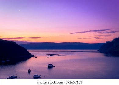 Boats in Portree bay during colorful sunrise with purple and orange colors with hills on both sides on the Isle of Skye