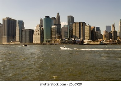Boats race in front of New York financial district skyline and South Street Seaport, view from Brooklyn