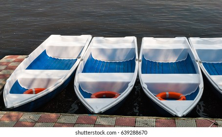 Boats for rent in a row on a lake.