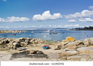 Boats, rocks and clouds on Abilleira beach at Arousa Island