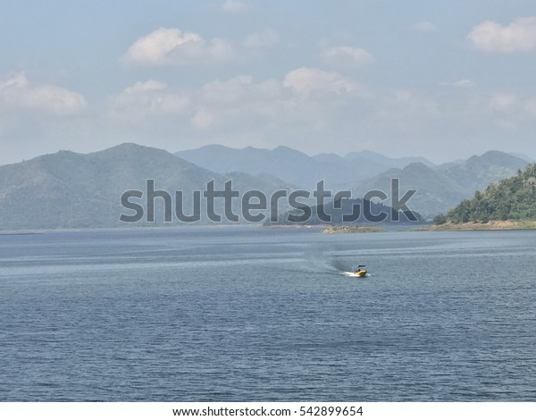 Boats sail in the water with mountains and sky.