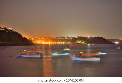 Boats sailing at Dona Paula view point at night in Panaji, Goa.