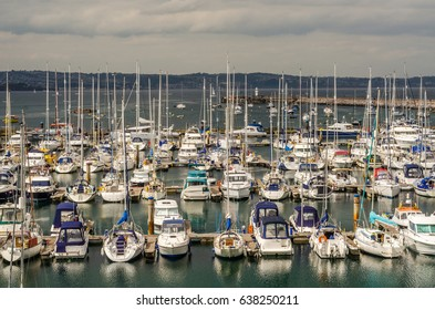 Boats and ships moored in a small port, in the background stone promenade and coastal town, fishing industry and tourism, travel