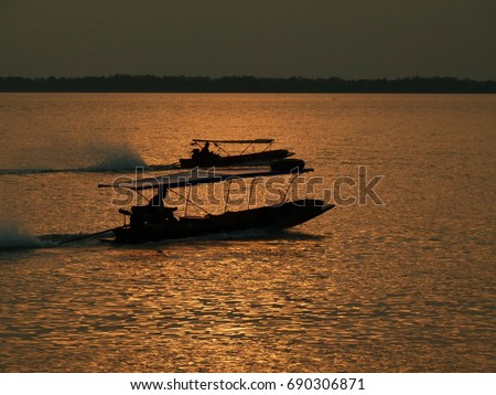 Boats in silhouette at sunset in Thailand