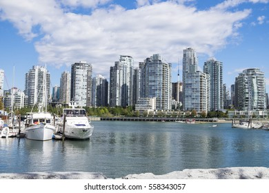 Boats sit idle in a marina on False Creek with the Vancouver's Yaletown neighborhood skyline in the background.