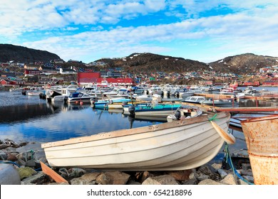 boats sit moored at the city habor. trading port with its docks more recently undergoing  qaqortoq greenland
