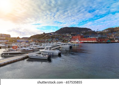 boats sit moored at the city habour. trading port with its docks more recently undergoing  qaqortoq greenland