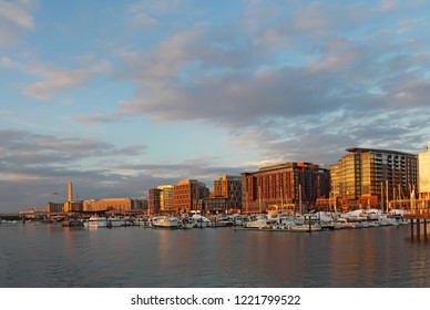Boats and skyline of buildings at the newly redeveloped Southwest Waterfront area of Washington, DC at sunset viewed from the water in fall with the Washington Monument in the background