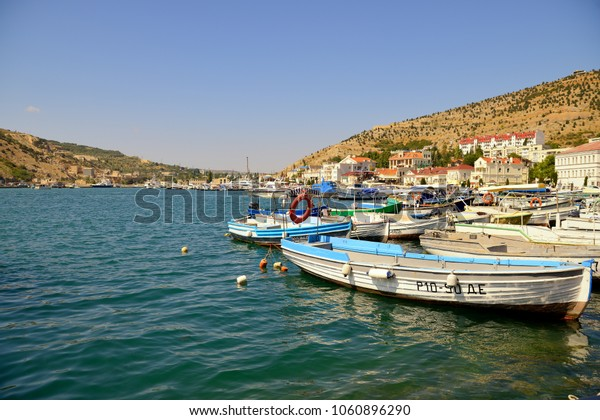 Boats stand in the Bay against the hills and the blue sky on a Sunny day. Horizontal view.