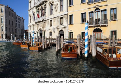 Boats tied to colorful bollanrds at a jetty of a hotel on the Grand Canal in Venice, Italy