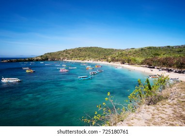 Boats with tourists arriving to beautiful beach on tropical island, Lombok, Indonesia