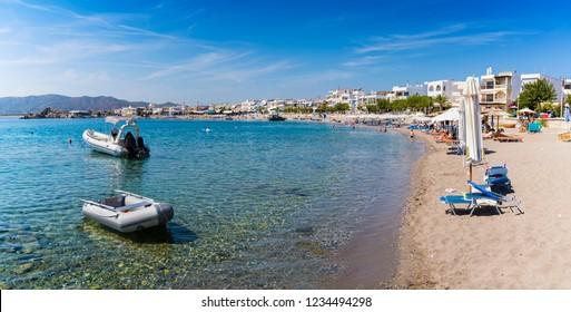 Boats and umbrellas in Haraki beach – sunny day (Rhodes, Greece)