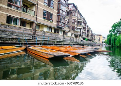 Boats used for tourism travel along  the River Cam  in Cambridge with old architecture building in  the county town of Cambridgeshire, England, north of London.