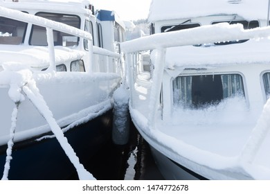 boats in winter, frozen and covered in snow