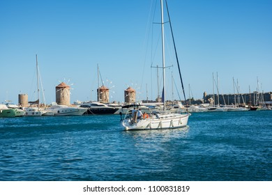 Boats, yachts and windmills in Mandraki harbor in City of Rhodes (Rhodes, Greece)