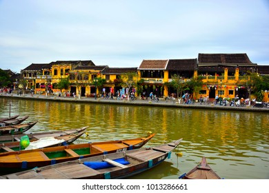 Boats and yellow colonial-style houses of Hoi An city, Vietnam.