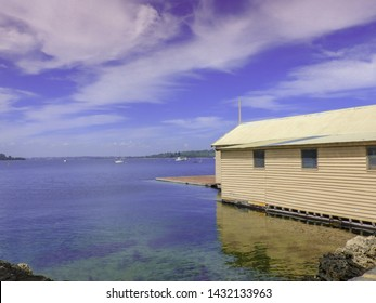 Boatshed on the Swan River, Perth, West Australia. Cream coloured building against dramatic cloud sky