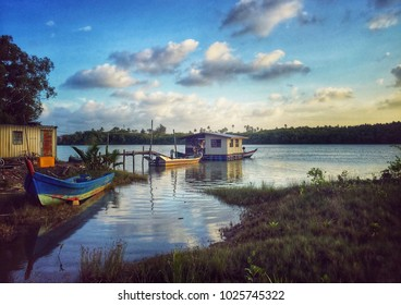 Boatshed with sunrise or sunset view at lakeside or river. Fishing boat and reflection of the sky and clouds.